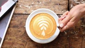 A mão da mulher põe a xícara de café em uns pires sobre uma tabela de madeira em uma cafetaria vídeos de arquivo