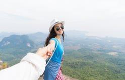 A mão da mulher da posse do homem, par do turista no sorriso feliz superior da montanha aprecia a paisagem bonita fotografia de stock royalty free