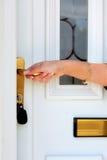 Mão da mulher que abre a porta Imagens de Stock