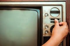Mão da mulher que ajusta a televisão do vintage com botão do controle Fotos de Stock