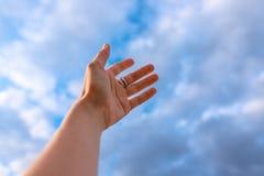 A mão da mulher que alcança para ao céu azul fotografia de stock