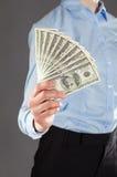 A mão da mulher que alcança para fora o dinheiro Imagens de Stock Royalty Free