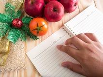 A mão da mulher que aponta no caderno vazio com fita do Natal Imagens de Stock Royalty Free