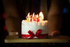 Mão da mulher que dá o bolo de aniversário delicioso com velas ardentes Foto de Stock Royalty Free