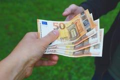 Mão da mulher que dá o dinheiro fotografia de stock