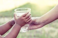 Mão da mulher que dá o vidro da água fresca à criança no parque Fotografia de Stock Royalty Free