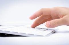 Mão da mulher que datilografa no teclado de computador
