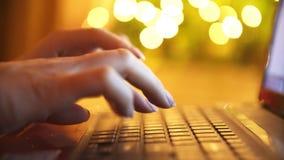 A mão da mulher que datilografa no teclado do portátil Festões em um fundo video estoque