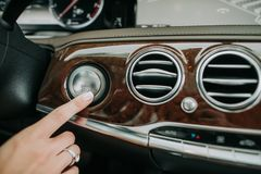 Mão da mulher que empurra no botão do carro do começo fotografia de stock royalty free