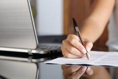 Mão da mulher que escreve um contrato com um portátil ao lado