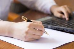 Mão da mulher que escreve um contrato com um portátil ao lado Foto de Stock
