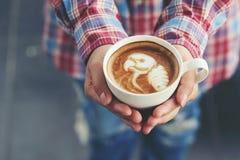 Mão da mulher que guarda a arte do latte do café com teste padrão o papagaio em c foto de stock royalty free