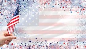 Mão da mulher que guarda a bandeira dos EUA no fundo dos fogos-de-artifício Fotografia de Stock Royalty Free