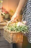 Mão da mulher que guarda a cesta das flores Foto de Stock