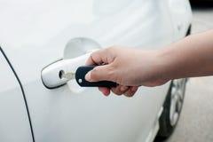 Mão da mulher que guarda chaves do carro para destravar ou travar foto de stock