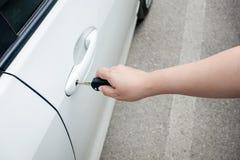 Mão da mulher que guarda chaves do carro para destravar ou travar fotos de stock