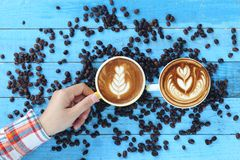 Mão da mulher que guarda dois copos da arte do latte com teste padrão as folhas imagens de stock royalty free