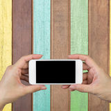 Mão da mulher que guarda e que usa o móbil, telefone celular, telefone esperto com a tela isolada em pranchas pintadas e em pranc Fotografia de Stock Royalty Free