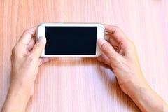 Mão da mulher que guarda e que usa o telefone esperto na madeira da tabela Fotos de Stock Royalty Free