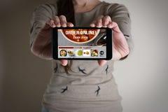Mão da mulher que guarda móvel com o alimento da ordem em linha Fotos de Stock Royalty Free
