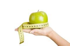 Mão da mulher que guarda a maçã e que mede a fita Foto de Stock Royalty Free