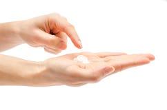 Mão da mulher que guarda a nata dos cuidados com a pele imagem de stock