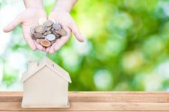 A mão da mulher que guarda o banco da casa das moedas salvar o dinheiro, fundo verde da natureza Fotografia de Stock Royalty Free