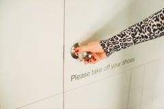 Mão da mulher que guarda o botão de porta, abertura ou fechando a porta, com prisão militar imagens de stock royalty free