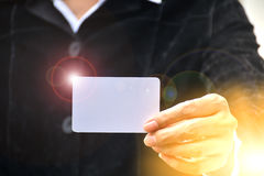 Mão da mulher que guarda o canto branco da luz do alargamento do cartão do cartão Foto de Stock