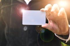 Mão da mulher que guarda o canto branco da luz do alargamento do cartão do cartão Imagem de Stock Royalty Free