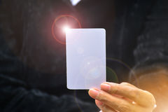 Mão da mulher que guarda o canto branco da luz do alargamento do cartão do cartão Foto de Stock Royalty Free