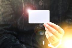 Mão da mulher que guarda o canto branco da luz do alargamento do cartão do cartão Fotos de Stock