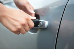 Mão da mulher que guarda o carro chave para destravar, fotos de stock