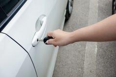 Mão da mulher que guarda o carro da porta para destravar ou travar imagens de stock royalty free