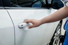 Mão da mulher que guarda o carro da porta para destravar ou travar imagens de stock