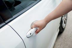 Mão da mulher que guarda o carro da porta para destravar ou travar imagem de stock royalty free