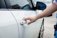 Mão da mulher que guarda o carro da porta para destravar ou travar fotos de stock