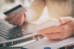 A mão da mulher que guarda o cartão de crédito e o smartphone imagens de stock