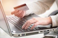A mão da mulher que guarda o cartão de crédito sobre o portátil imagens de stock royalty free
