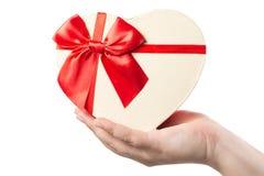 A mão da mulher que guarda o coração deu forma à caixa atual com a fita vermelha isolada no fundo branco fotografia de stock royalty free