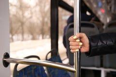 A mão da mulher que guarda o corrimão no ônibus imagens de stock royalty free