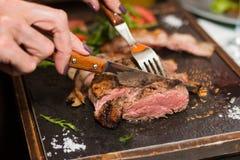 A mão da mulher que guarda o corte da faca e da forquilha grelhou o bife foto de stock
