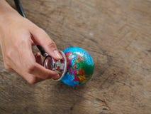 Mão da mulher que guarda o estetoscópio com o globo na parte traseira de madeira da textura foto de stock
