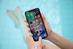Mão da mulher que guarda o iPhone X com IOS 11 na tela imagem de stock