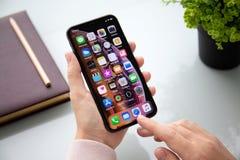 Mão da mulher que guarda o iPhone X com IOS da tela home fotos de stock royalty free