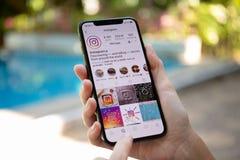 Mão da mulher que guarda o iPhone X com serviço social Insta dos trabalhos em rede imagens de stock