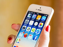 Mão da mulher que guarda o iPhone 5S de Apple Foto de Stock Royalty Free