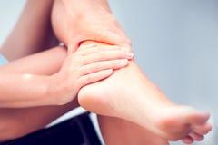 Mão da mulher que guarda o pé com dor, cuidados médicos e o conce médico foto de stock royalty free
