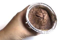 a mão da mulher que guarda o queque do chocolate Fotografia de Stock