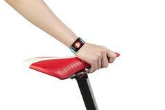 Mão da mulher que guarda o relógio esperto vestindo do sensor da saúde do assento da bicicleta Fotos de Stock